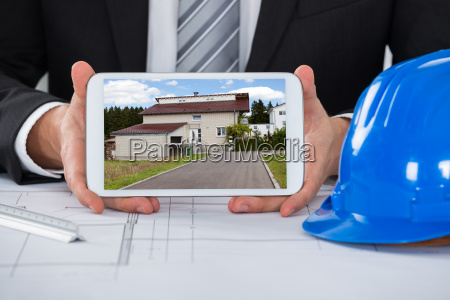 male architect showing picture of house