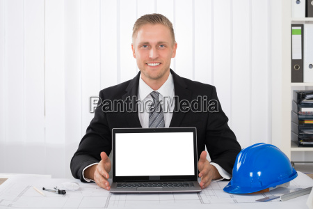 architect showing his laptop over blue