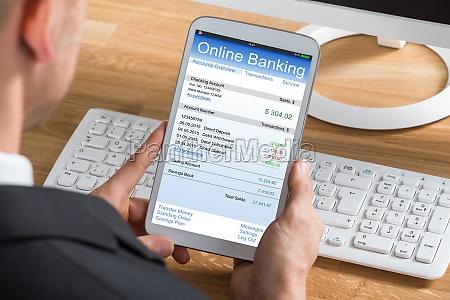 wirtschaftler online banking mit digitalen tablet