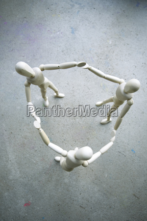 three wooden manikins holding hands on
