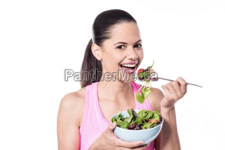 pretty woman eating green salad