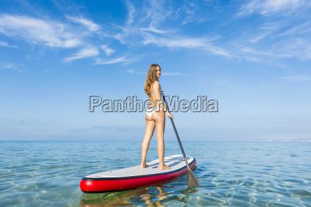 frau entspannt ueber einem paddel surfbrett