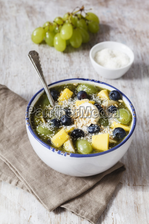 bowl of green smoothie and fruits