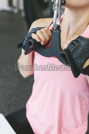 frau macht latziehen in fitness studio