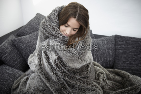 young woman on couch wrapped in