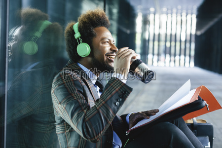 smiling young businessman with coffee to