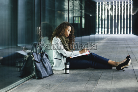 young businesswoman sitting outdoors writing in