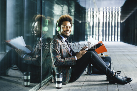 smiling young businessman with headphones and