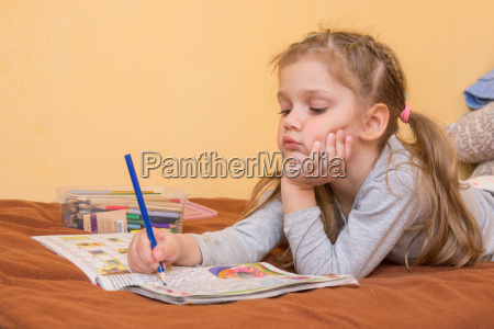 little girl studying a magazine with