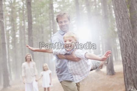 father flying son in sunny woods