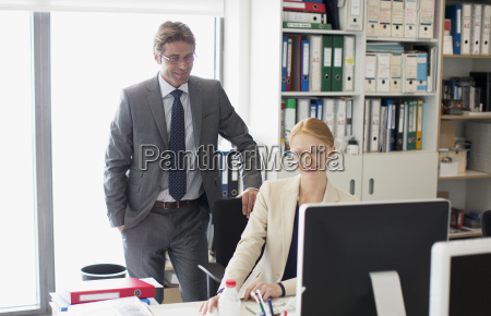 businessman and businesswoman using computer at