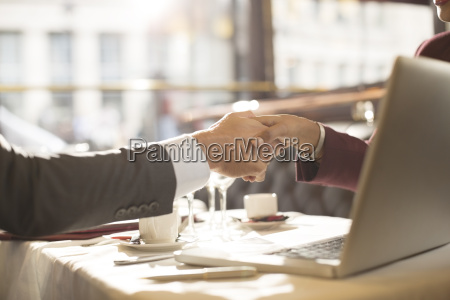 business people shaking hands in restaurant
