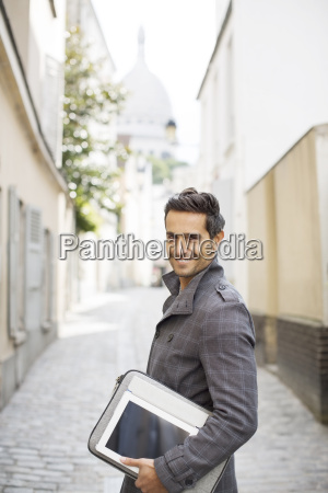 businessman carrying digital tablet on city