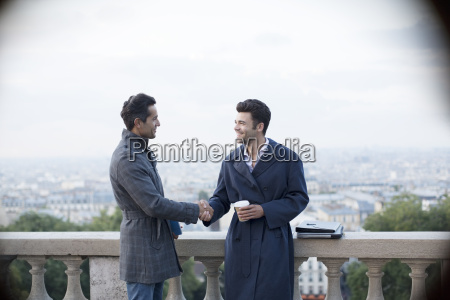 businessmen shaking hands at railing overlooking