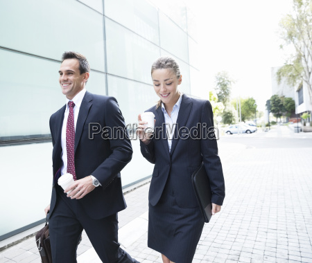 smiling businessman and businesswoman walking with