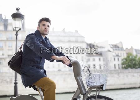 geschaeftsmann fahren fahrrad entlang fluss seine
