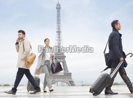 business people walking near eiffel tower