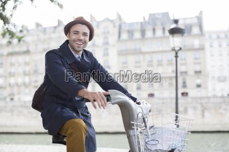 geschaeftsmann auf dem fahrrad entlang fluss