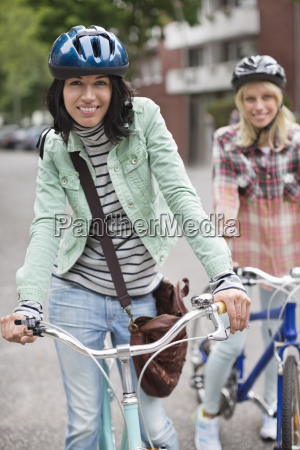 women pushing bicycles on city street