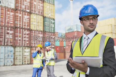businessman using digital tablet near cargo