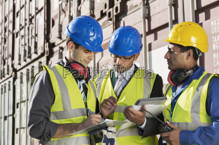 businessmen and worker talking near cargo