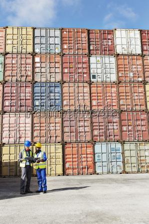 businessman and worker talking near cargo