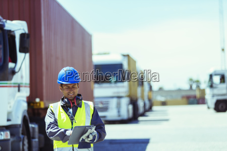 worker using digital tablet near trucks