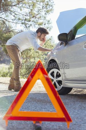mann am strassenrand kontrolliert autotrootor hinter