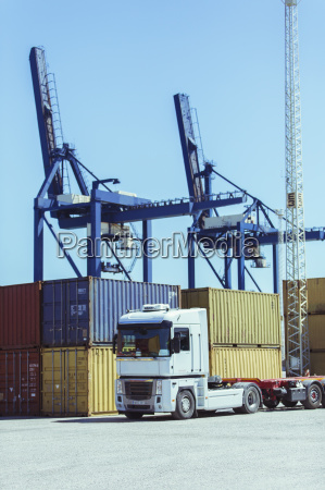 cranes over cargo containers and truck