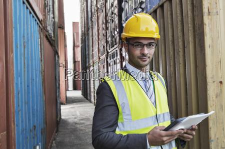 businessman holding digital tablet between cargo