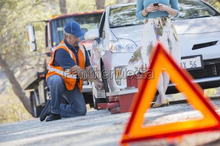 strassenmechaniker wechselnden reifen hinter dem warndreieck