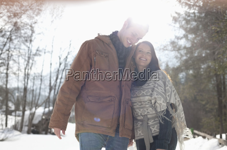 happy couple hugging in snowy woods