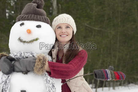 happy woman hugging snowman in woods