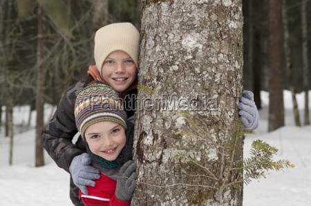 portrait of happy boys behind tree
