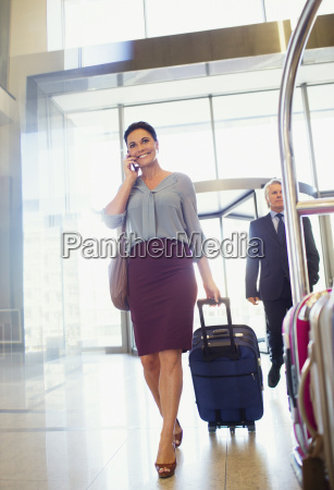 business woman pulling suitcase and using