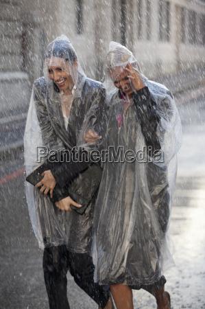 businesswomen in ponchos walking in rainy