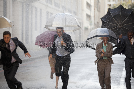 enthusiastic business people with umbrellas running