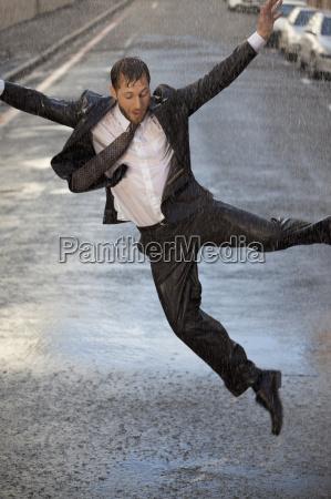 enthusiastic businessman dancing in rainy street