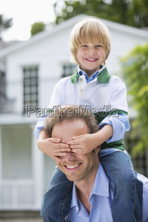 boy covering fathers eyes outdoors