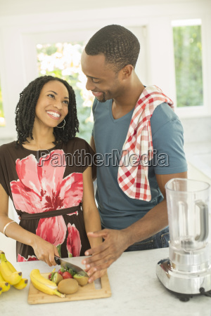 happy couple slicing fruit next to