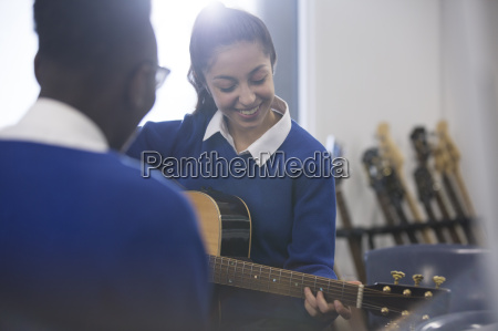 students playing acoustic guitar in classroom