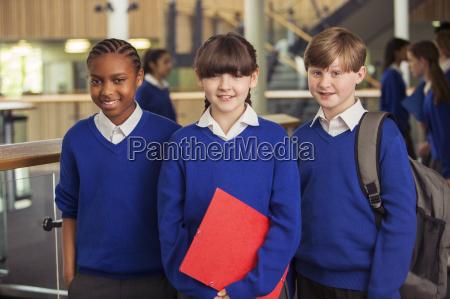 portraet von drei grundschulkindern in blauen