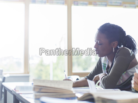 female student writing at desk in