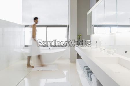 man in towel walking in bathroom