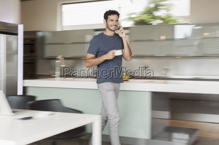 smiling man drinking coffee and talking
