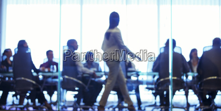 businesswoman walking in front of colleagues