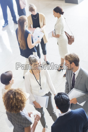 businesswoman talking to conference participants standing