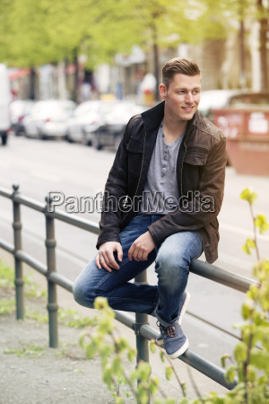 young blonde man sitting outside