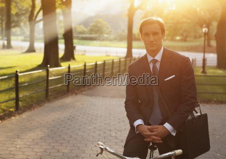 businessman sitting on bicycle in urban