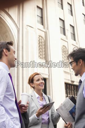 business people talking on city street